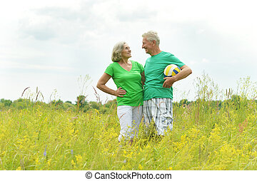 Senior couple in field with ball