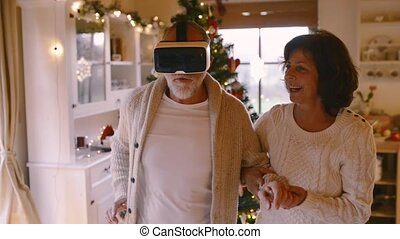 Senior couple in front of Christmas tree. Man with VR goggles.