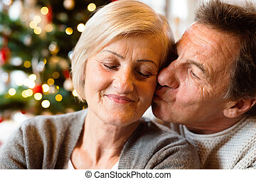 Senior couple in front of Christmas tree kissing, close up....
