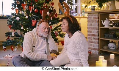 Senior couple in front of Christmas tree wearing deer antlers.