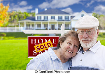 Senior Couple in Front of Sold Real Estate Sign and House