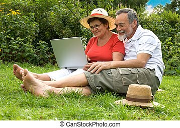 senior couple in garden at leisure with laptop computer
