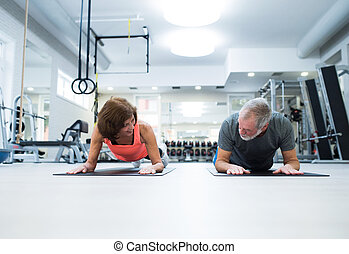 Senior couple in gym in plank position working abs