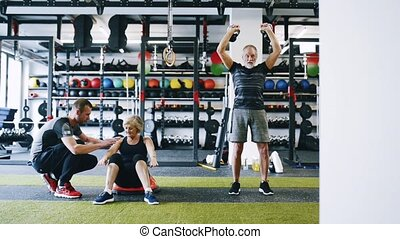 Senior couple in gym with personal trainer doing various exercises