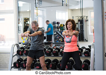 Senior couple in gym working out using kettlebells. -...