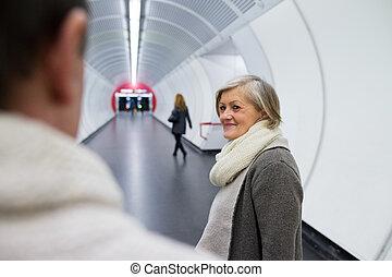Senior couple in hallway of subway saying goodbye
