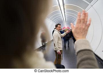 Senior couple in hallway of subway saying goodbye -...