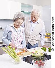 senior couple in kitchen - senior asian couple preparing...