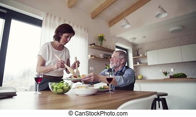 Senior couple in love serving lunch indoors at home,...