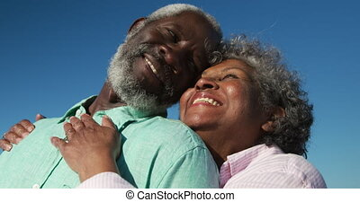 Senior couple in love smiling at the beach