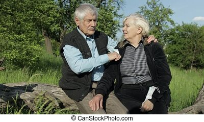 Senior grandparents couple in medical masks sitting in park during COVID-19 coronavirus pandemic. Take off masks, hugs and kiss each other. Social distancing and self isolation in quarantine lockdown