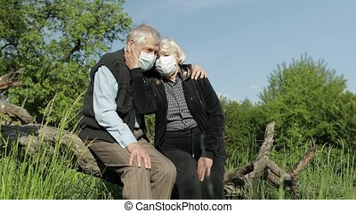 Senior old grandparents couple in medical masks sitting in park during COVID-19 coronavirus pandemic. Embracing, hugs each other in garden. Social distancing and self isolation in quarantine lockdown
