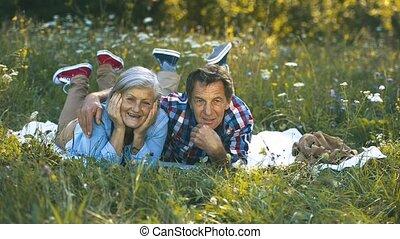 Senior couple in nature lying on a blanket, having picnic