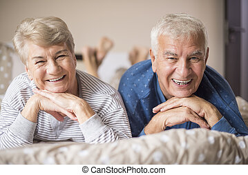 Senior couple in pajamas on the bed