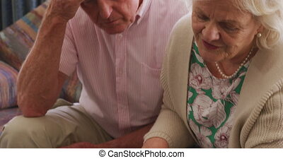Senior Caucasian couple spending time at home together, sitting on a couch, using a laptop computer, social distancing during coronavirus covid19 pandemic.