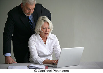 Senior couple in suit in front of a laptop computer