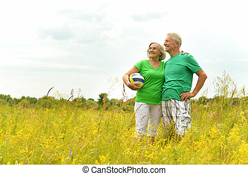 Senior couple in summer field with ball