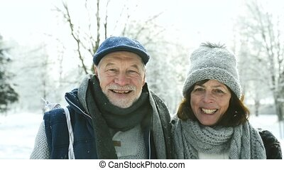 Senior couple in sunny winter nature.