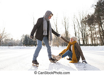 Beautiful senior couple in sunny winter nature ice skating, man helping woman to stand up.