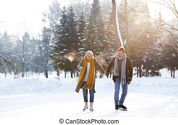 Beautiful senior woman and man in sunny winter nature ice skating.