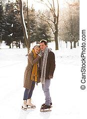 Senior couple in sunny winter nature ice skating, hugging. -...