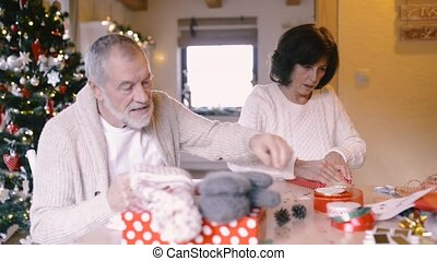 Senior couple in sweaters wrapping Christmas gifts together.