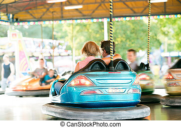 Senior couple in the bumper car at the fun fair - Senior...