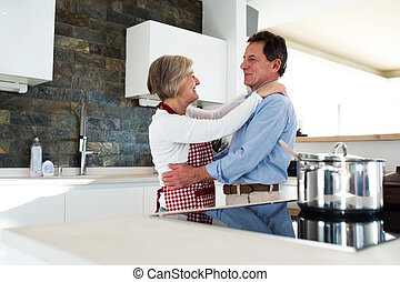 Senior couple in the kitchen cooking and dancing together.