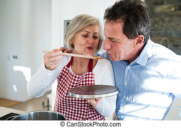 Senior couple in the kitchen cooking together.