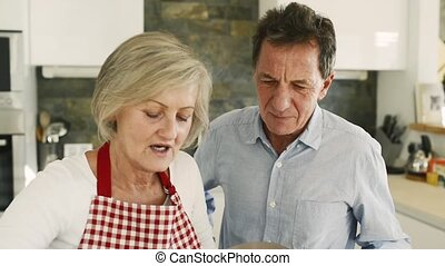 Senior couple in the kitchen cooking together. - Senior...