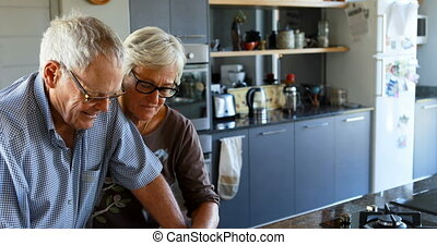Senior couple interacting each other in kitchen 4k