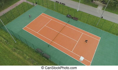 Senior couple is playing tennis on court in green park. Aerial vertical top view. Drone is flying around.