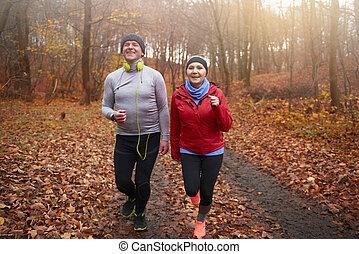 Senior couple jogging among forest path