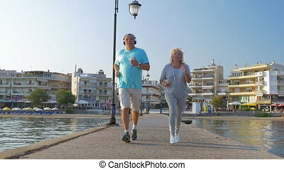 Senior couple jogging with music on the pier