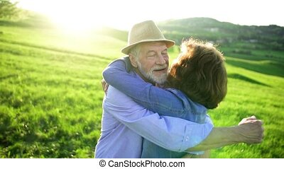 Senior couple kissing and hugging outside in spring nature...