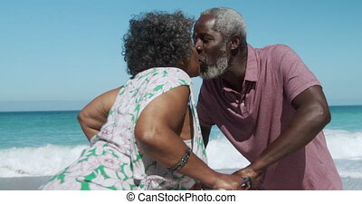 Senior couple kissing at the beach - Side view of a senior ...