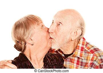 Senior couple kissing - Happy senior couple on white...