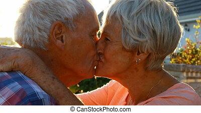 Senior couple kissing in backyard 4k