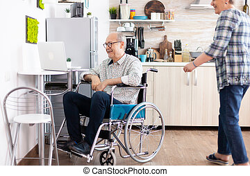 Senior couple laughing using laptop, husband calling his wife near him during a video call with grandchildrens sitting in kitchen. paralyzedhandicapped old elderly man using communication techonolgy
