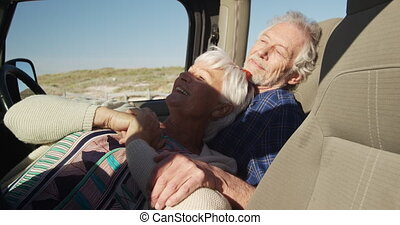 Senior couple leaning together in a car