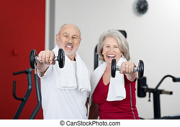 Senior Couple Lifting Dumbbells In Gym