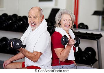 Senior Couple Lifting Dumbbells While Sitting In Gym