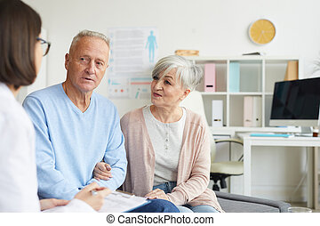 Senior Couple Listening to Doctor in Clinic