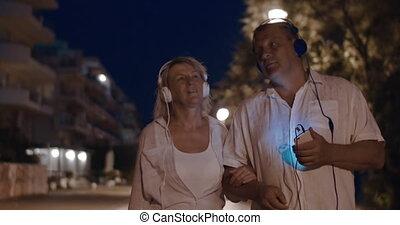 Senior couple listening to music during night walk