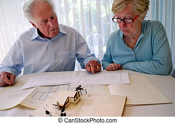 senior couple looking at a ground plan and house model