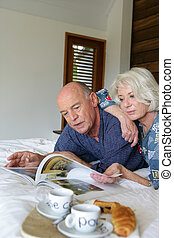 Senior couple looking at a magazine in bed