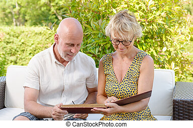 senior couple looking at a picture book, sitting in a sofa