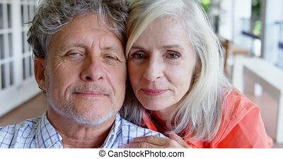 Senior couple looking at camera on the porch at home 4k -...