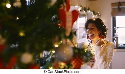 Senior couple looking at Christmas tree at home.