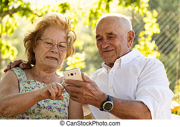 senior couple looking at mobile phone